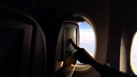 Dziewczyna lata w samolocie i ogląda środek zawartość na samolocie zdjęcie wideo