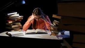 Dziewczyna leafing przez książki uśpionych przy stołem spadać i Czarny tło zdjęcie wideo