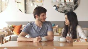 Dziewczyna mówi coś jej przyjaciel przy kawiarnią zdjęcie royalty free