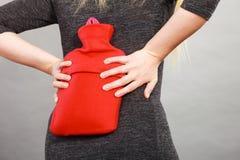 Dziewczyna ma ból pleców, trzyma gorącej wody butelkę Obrazy Royalty Free