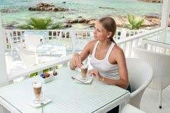 Dziewczyna ma kawową przerwę w widok na ocean kawiarni obraz royalty free