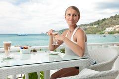 Dziewczyna ma kawową przerwę w widok na ocean kawiarni zdjęcia royalty free