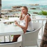 Dziewczyna ma kawową przerwę w widok na ocean kawiarni obraz stock