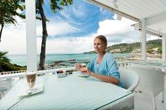 Dziewczyna ma kawową przerwę w widok na ocean kawiarni fotografia royalty free