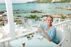 Dziewczyna ma kawową przerwę w widok na ocean kawiarni zdjęcie royalty free
