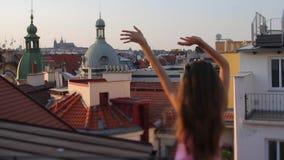 Dziewczyna macha jej ręki przeciw tłu miasto zbiory wideo