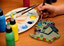 Dziewczyna maluje glinianą zabawkę Zdjęcia Royalty Free