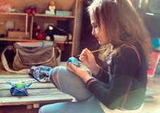 Dziewczyna maluje jajko dla wielkanocy indoors Fotografia Royalty Free