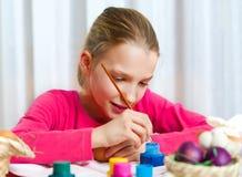 Dziewczyna maluje Wielkanocnego jajko Fotografia Stock