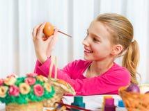 Dziewczyna maluje Wielkanocnego jajko Obraz Royalty Free