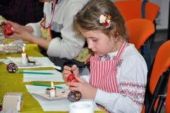 Dziewczyna maluje Wielkanocnego jajko Zdjęcia Royalty Free