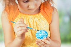 Dziewczyna maluje Wielkanocnego jajko w błękitnym kolorze Zdjęcie Stock