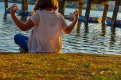Dziewczyna medytuje jeziorem podczas złotej godziny zdjęcie stock