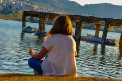 Dziewczyna medytuje jeziorem podczas złotej godziny obrazy royalty free