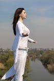 Dziewczyna medytuje na wzgórzu przeciw niebieskiemu niebu Zdjęcia Royalty Free