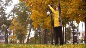 Dziewczyna medytuje w jesień parku z ona ręki up zbiory wideo