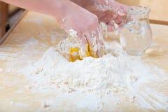 Dziewczyna miesza ręką wodę, mąkę i jajko, obrazy royalty free