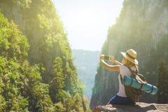 Dziewczyna modnisia podróżnik bierze obrazki natura na tle góra Turystyczny podróżnik na tło dolinie fotografia royalty free