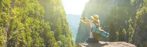 Dziewczyna modnisia podróżnik bierze obrazki natura na tle góra Turystyczny podróżnik na tło dolinie zdjęcie stock