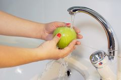 Dziewczyna myje jabłka pod klepnięciem Zdjęcia Stock