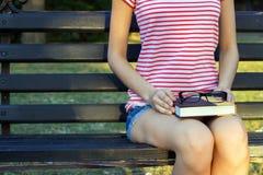 Dziewczyna na ławce w parku z książkowymi i czarnymi szkłami w ona podołek Uczeń w parkowym czytaniu książka fotografia stock