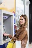 Dziewczyna na atm maszynowej bierze gotówce zdjęcia stock