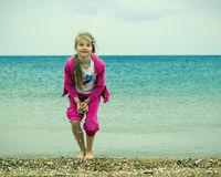 Dziewczyna na dennym brzeg, przygotowywającym rzucać up garść skorupy zdjęcia royalty free