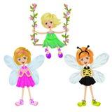dziewczyna na huśtawce i dwa dziewczynach z czarodziejskimi skrzydłami na bielu Zdjęcia Royalty Free