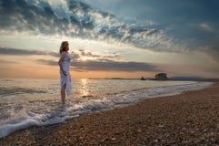 Dziewczyna na idyllicznej plaży w fala przy pięknym wschodem słońca Zdjęcie Stock