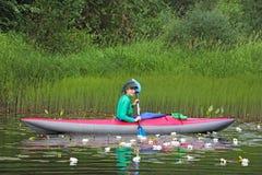 Dziewczyna na kajaku wśród wodnych leluj Zdjęcia Stock