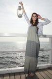 Dziewczyna na molu z nafty lampą Fotografia Stock