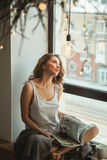 Dziewczyna na okno z magazynem i filiżanką kawy Zdjęcia Stock