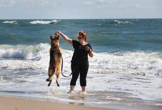Dziewczyna na plaży z psem w kipieli fotografia royalty free