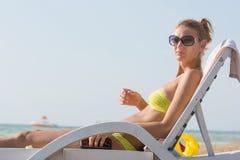 Dziewczyna na pokładu krześle na plaży iść robić manicure'owi Zdjęcia Stock