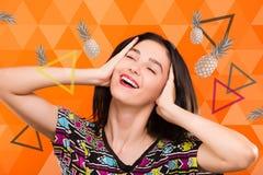 Dziewczyna na pomarańczowym geometrycznym tle z kolorowymi trójbokami i Zdjęcie Royalty Free