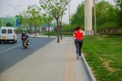 Dziewczyna na ranku bieg na drodze blisko parka fotografia royalty free