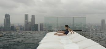 Dziewczyna na recliner obok basenu obraz stock