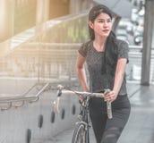 Dziewczyna na rowerze w mieście w ranku z słońce racą fotografia stock