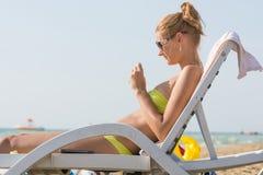 Dziewczyna na słońca lounger obok morza robi manicure'owi Zdjęcie Royalty Free