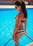 Dziewczyna na schodkach wchodzić do pływackiego basenu Zdjęcie Stock