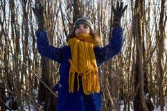 Dziewczyna na spacerze w parku w zimie w opadzie śniegu Jest ubranym purpurowego żakiet, szarego koloru żółtego szalika i kapelus obraz stock