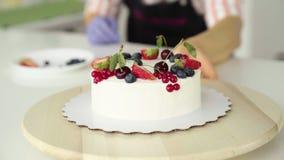 Dziewczyna naczelna cukierniczka, dekoruje lasowe jagody, truskawki, domowej roboty tort zbiory