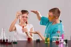 Dziewczyna nalewa czerwonego ciecz od pomiarowej pipety w szklaną kolbę facetów przedstawienia jego ręki rozmiar Zdjęcia Stock