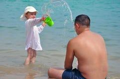 Dziewczyna nalewa wodę na jej ojcu Pluśnięcia woda w morzu Dziecko i ojciec na wakacje obraz stock