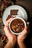 Dziewczyna napojów gorącej czekolady kubek z boże narodzenie teraźniejszością na wieśniaku, Obraz Royalty Free