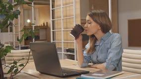 Dziewczyna napoju kawa przy pracującym centrum zbiory