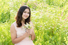 Dziewczyna nastolatek z bukietem stokrotki na lato łące Obrazy Stock
