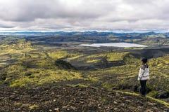 Dziewczyna nastolatek zostaje w skłonie stawia czoło Południowo-zachodni część Lakagigar powulkaniczna szczelina w południe Icela fotografia stock