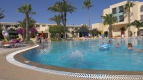 Dziewczyna nastolatka doskakiwanie w wodnym pływackim basenie w hotelu Szczęśliwa dziewczyna w szkłach w pływać plenerowego basen zbiory wideo