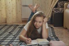 Dziewczyna nastoletnia co wydają czas rysuje w domu na podłoga podczas gdy kłamający Zdjęcie Stock
